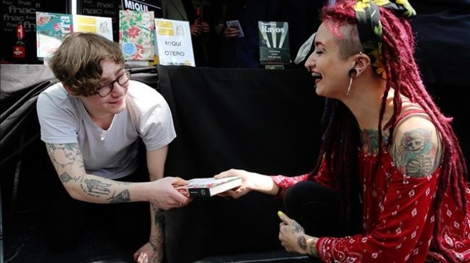Ben Brooks entrega un libro a una admiradora por debajo de la mesa.