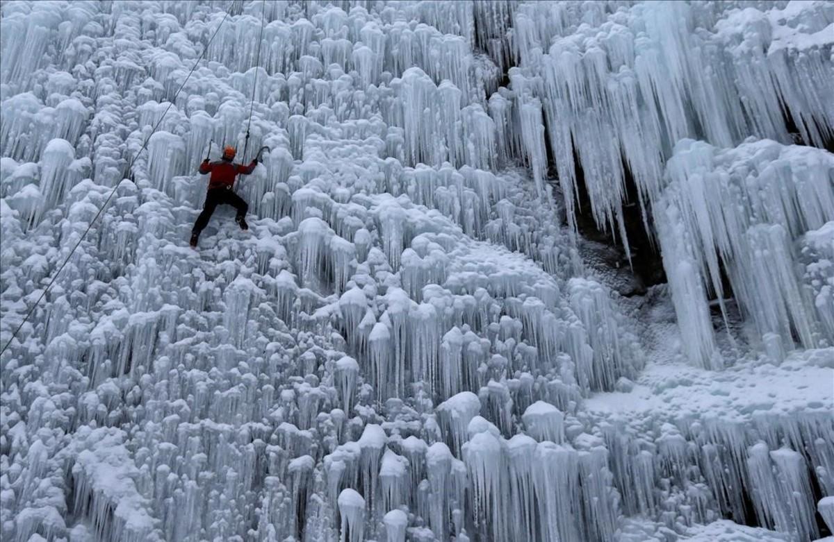 Un hombre escala una pared artificial de hielo en la ciudad de Liberec, República Checa.