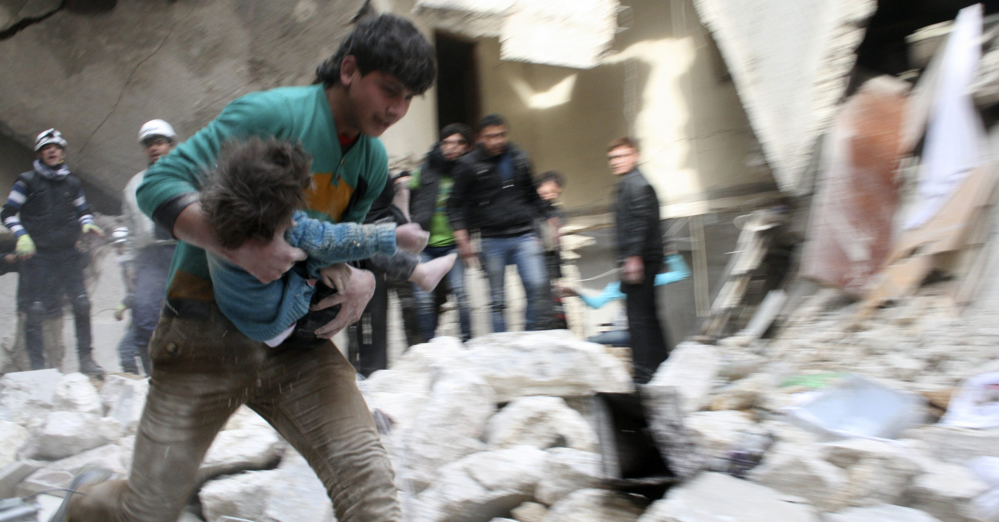 Un hombre traslada a una ni�a herida tras un bombardeo en Alepo.