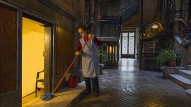 Una mujer friega el suelo de una portería de la calle de Mallorca.