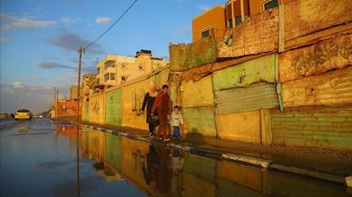 Palestins caminen per uncarrer al campde refugiats d'Al-Xatee, ala ciutatde Gaza.