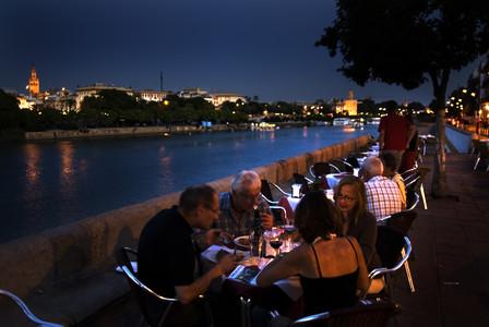Unos turistas cenan en una terraza de la calle Betis de Sevilla, con vistas al río Guadalquivir y con la Giralda y la Torre del Oro al fondo.