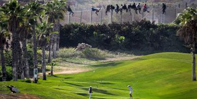Un grupo de inmigrantes tratan de saltar la valla de Melilla junto a un campo donde juegan dos golfistas.