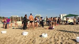 Los voluntarios durante la recogida de residuos del fondo mario de la playa de la Mar Bella.