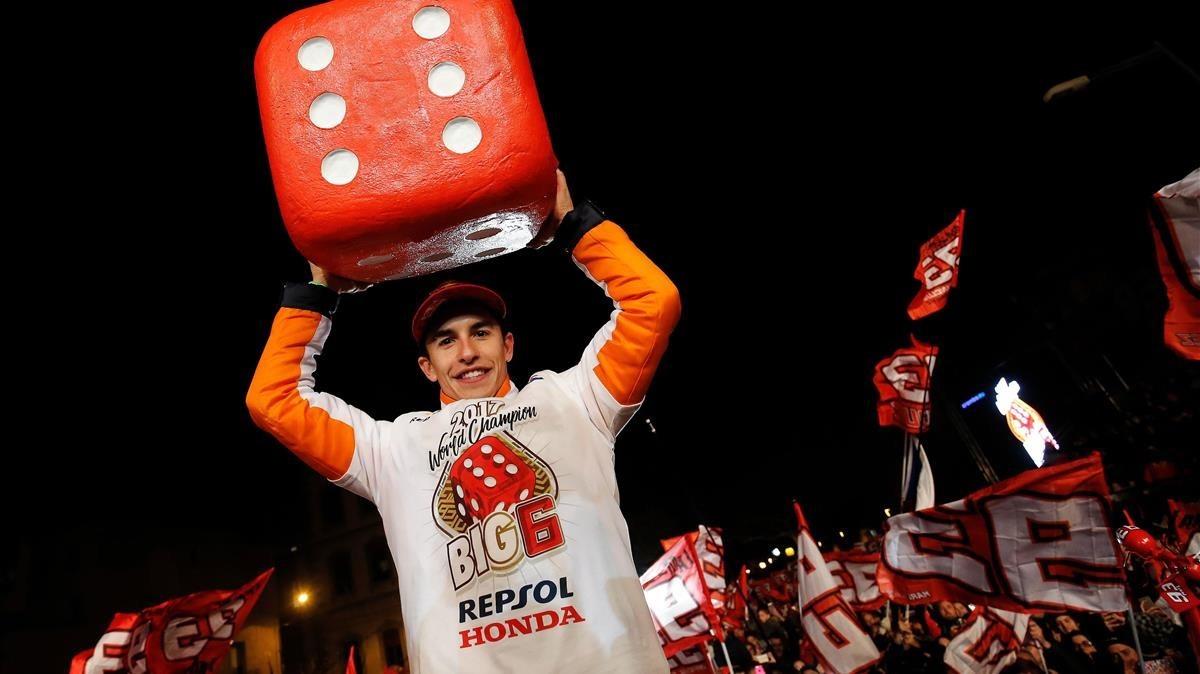 Márquez sostiene en Cervera un gran dado con los seis títulos que ha ganado.