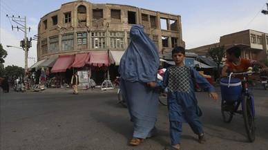 Una mujer afgana vestida con un burka agarra de la mano a su hijo al cruzar una calle en Herat, Afganist�n, este jueves.