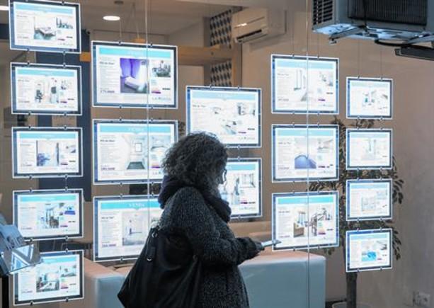 Una mujer consulta las ofertas inmobiliarias en el escaparate de una agencia.