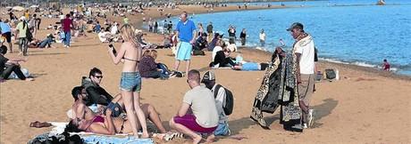 Turistas en la playa de la Barceloneta, ayer, aprovechando el d�a radiante.