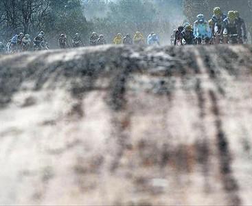 Los coches de los directores levantan polvo en los tramos de tierra, tras los ciclistas.