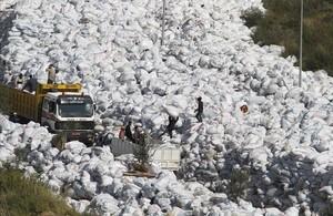 Varios operarios depositan bolsas de basuras sobre la gran montaña de residuos apilados en una calle del barrio de Al Fanar, en Beirut, este viernes.