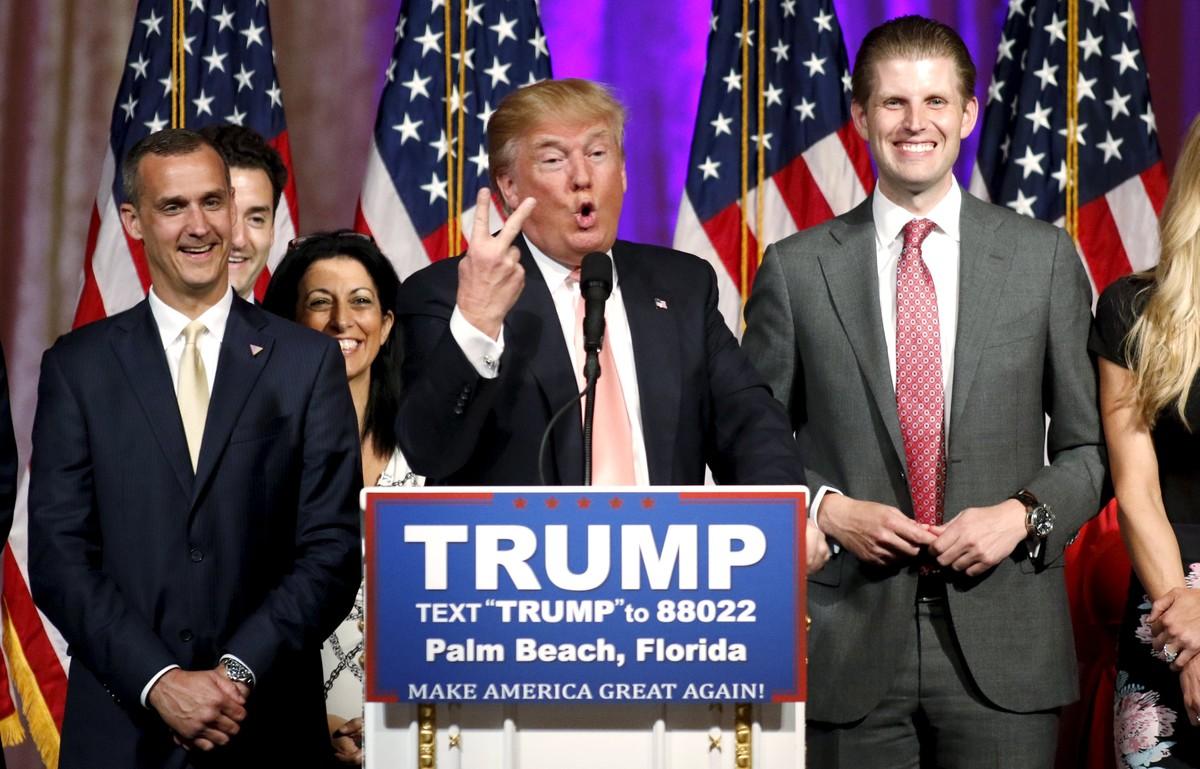 Donald Trump, flanqueado por su jefe de campaña, Corey Lewandowski (izquierda) y su hijo Eric (derecha), habla de los resultados de las primarias, anoche en Palm Beach (Florida).