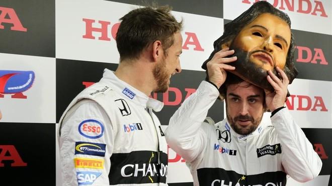 Fernando Alonso se coloca una máscara de sí mismo junto a Jenson Button durante la fiesta de fin de temporada de Honda en Motegi.