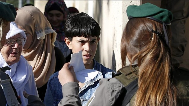 Un nino palestino muestra su carnet de identidad a una agente israel�mientras espera para poder cruzar a Jerusalen a trav�s del puesto de control de Bel�n.