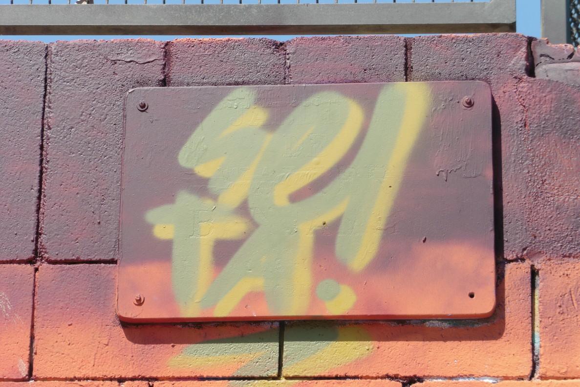La placa dels Jardins de Walter Benjamin, tapada per un grafiti