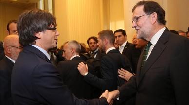 Puigdemont y Rajoy se saludan en el acto de inauguración de una exposición sobre Joan Miró en Oporto, el pasado septiembre.