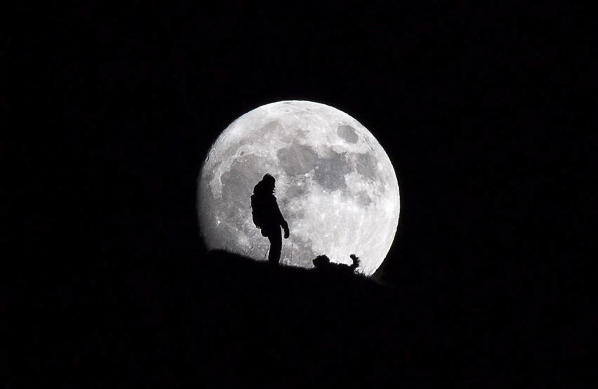 Silueta de una mujer mientras pasea a su perro con la luna llena como telón de fondo en la cumbre de Croix des Chaux, en los Alpes Suizos.