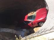 El coche fue engullido por el socavón que alcanzó casi toda la carretera.