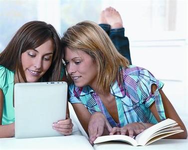 Dos jóvenes, con un libro y una tableta digital, dos formas de leer.