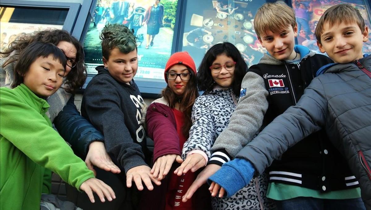 Un grupo de niños, algunos de ellos con fisura labial, juntan sus manos antes de entrar en el cine para ver la película Wonder, el domingo pasado en Cerdanyola.