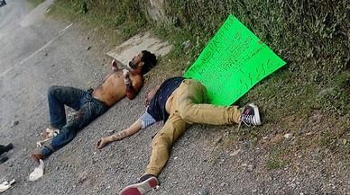 Dos de las v�ctimas en el suelo, junto a un cartel que les acusa de ladrones, firmado por un grupo de justicieros, este lunes en Guadalajara (M�xico).