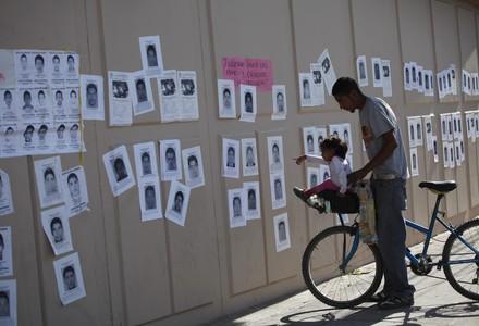 Una ni�a se�ala fotograf�as de los estudiantes desaparecidos, este jueves en un mural en Ciudad Ju�rez.