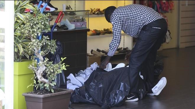 Un mantero carga una bolsa con decenas de zapatillas de deporte adquiridas a un mayorista chino ubicado en la avenida del Maresme del pol�gono Badalona Sud, el viernes.