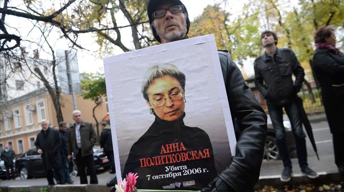 Un hombre sostiene una foto de Politkóvskaya en una concentración en su recuerdo el viernes en Moscú.