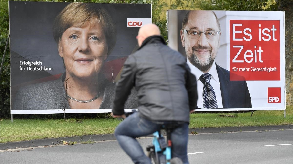 Un ciclista pasa frente a dos carteles electorales de Merkel (izquierda) y Schulz, en Essen, el 14 de septiembre.