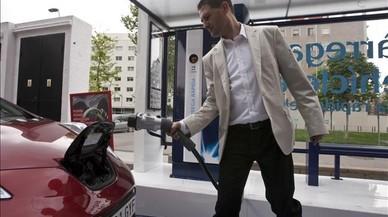 Un conductor carga su coche eléctrico en un punto de recarga de Barcelona.