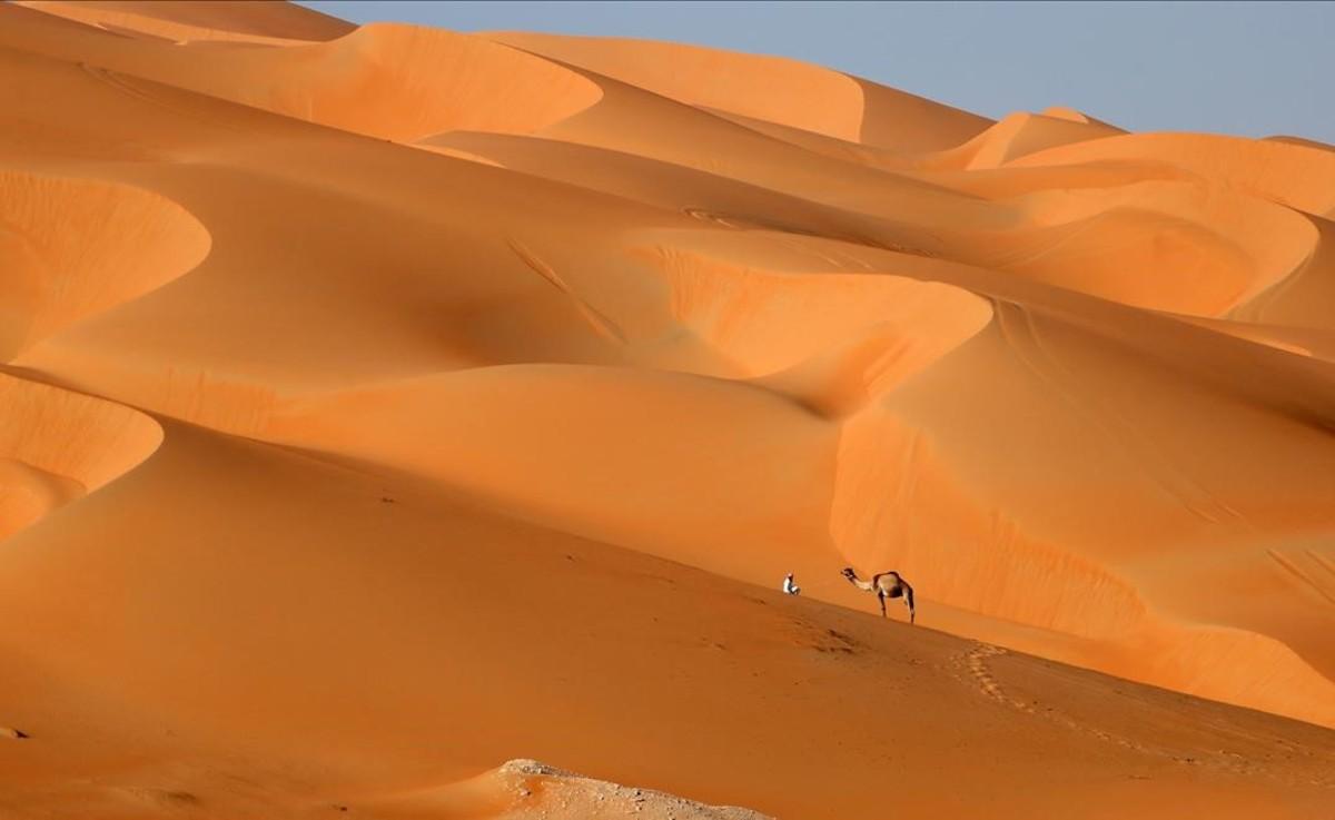 Un home camina amb el seu camell per les dunes del desert de Liwa, a l'emirat del golf d'Abu Dhabi.