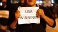 """Durante las celebraciones en Nueva York, un hombre sostiene un papel en el que puede leerse: """"Estados Unidos gana""""."""