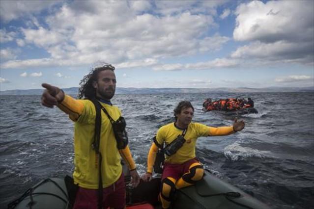 Dos miembros de Proactiva Open Arms socorren a refugiados en el Egeo.