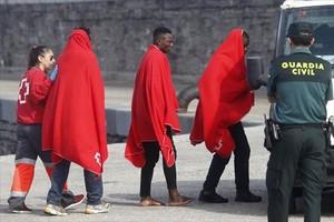 Un miembro de la Cruz Roja acompaña a varios de los subsaharianos rescatados, a su llegada a Tarifa.