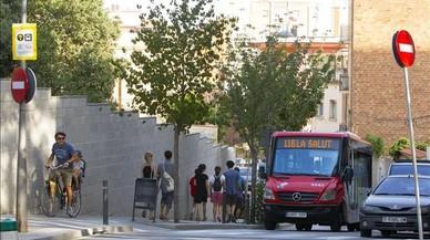 Unos turistas pasan a piejunto al autob�s de la l�nea 116 en su camino hacia el parque G�ell, este domingo.