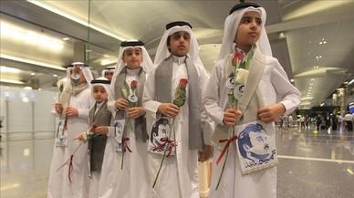 Niños qatarís con flores e imágenes del emir Al Thani reciben a ciudadanos de Kuwait y Omán, países que no se han sumado al boicot, en el aeropuerto de Doha.
