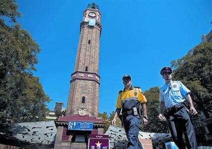 Un guardia urbano y un mosso d'esquadra patrullan el pasado agosto en Gràcia durante la fiesta mayor.