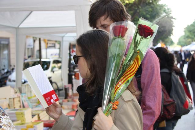 Una pareja compra las primeras rosas y libros en la diada de Sant Jordi 2014.