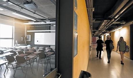 Tres estudiantes recorren un pasillo vac�o en la facultad de Geograf�a e Historia de la Universitat de Barcelona, donde a�n hay plazas vacantes, el pasado viernes.