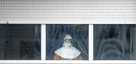 Un sanitario equipado con el traje de protecci�n mira hacia el exterior desde la sexta planta del Carlos III.