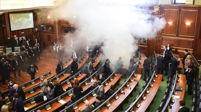Diputados kosovares evacúan la sala tras el lanzamiento del gas, en la primera sesión parlamentaria del año, en Pristina.