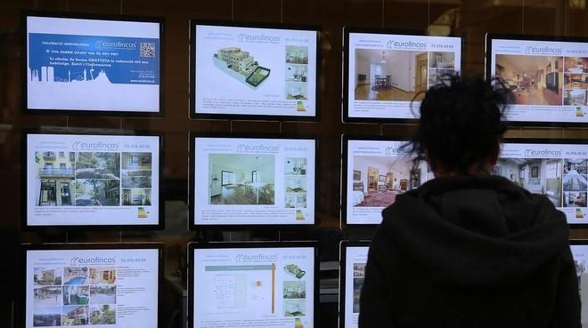 Una joven observa la oferta de pisos de una inmobiliaria del Eixample de Barcelona.