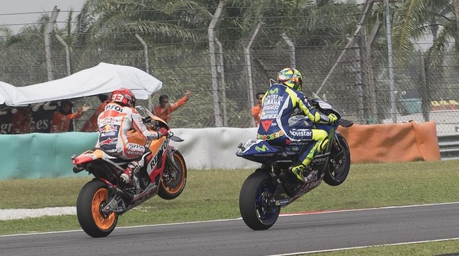 Msrc Márquez (Honda) y Valentino Rossi (Yamaha) levantan sus motos en homenaje a Simoncelli, hoy en Sepang.
