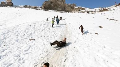 Nens afganesos es llancen per un pendent cobert de neu a Kabul (Afganistan).