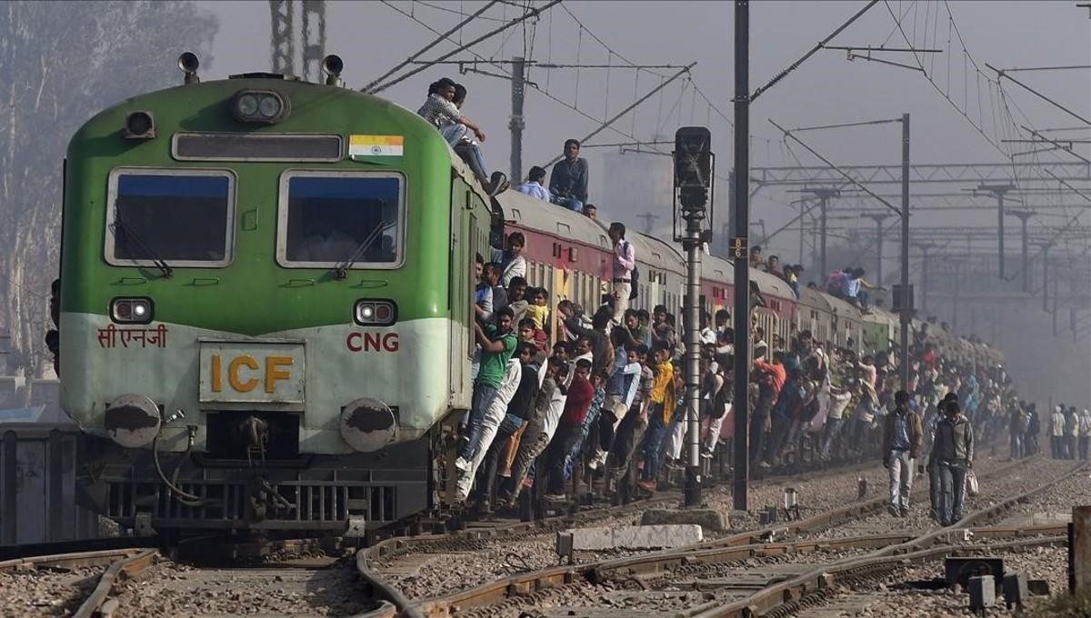Pasajeros indios se aferran a un tren enuna estación delas afueras de Nueva Delhi, India.