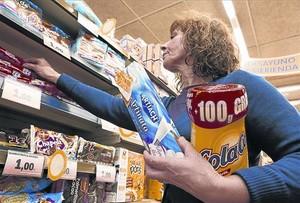 Una mujer compra Cola Cao y galletas Artiach, de Nutrexpa, en un supermercado.