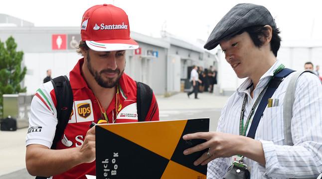 Fernando Alonso firma un autógrafo a un fan en el circuito de Suzuka