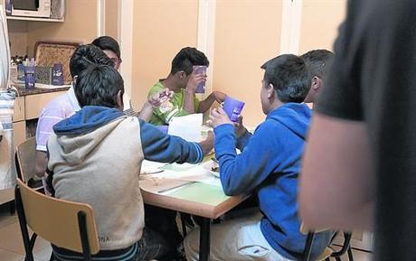 Un grupo de adolescentes, alumnos de instituto, toma el almuerzo en un centro abierto del barrio del Raval de Barcelona.