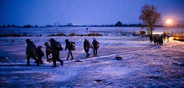 Migrantes y refugiados caminan por un campo cubierto de nieve tras cruzar la frontera de Macedonia con Serbia, cerca de la población de Miratovac, este domingo.