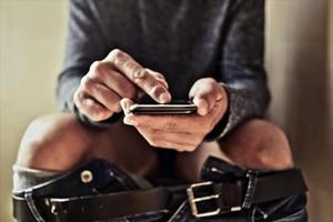 Un hombre usa el teléfono móvil en la intimidad del lavabo.