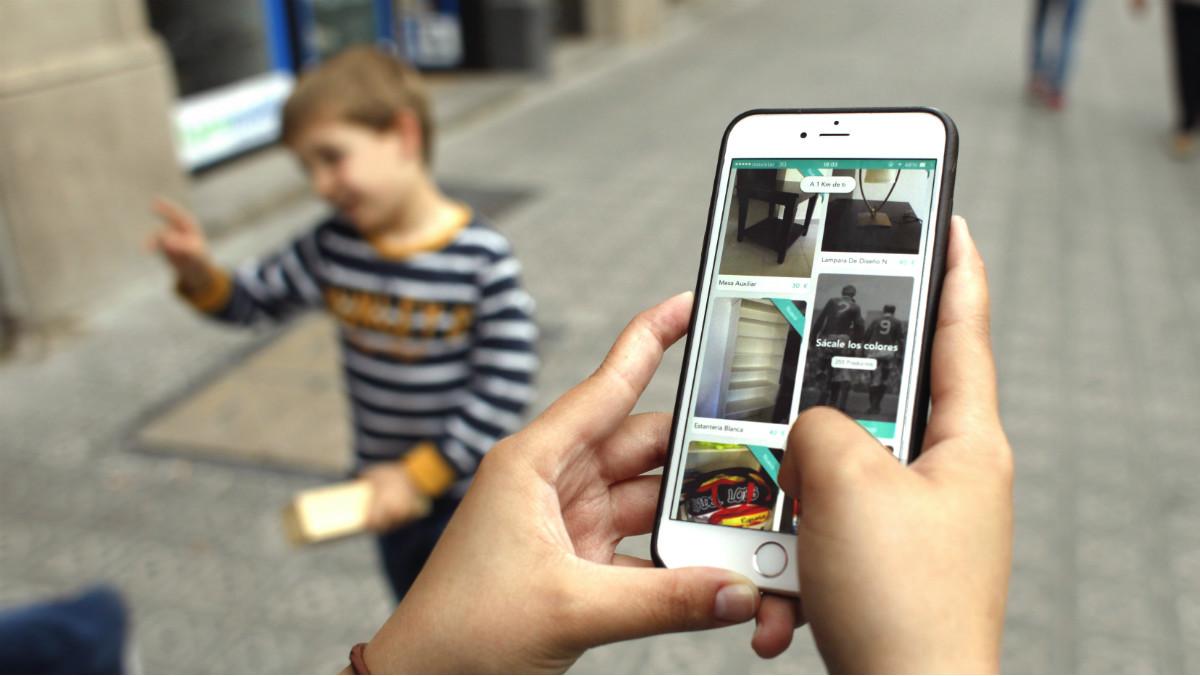 Un usuario consulta en su móvil el servicio de compraventas de Wallapop.